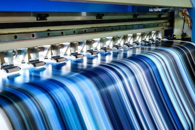 Großer tintenstrahldrucker, der mehrfarbig an vinylfahne arbeitet