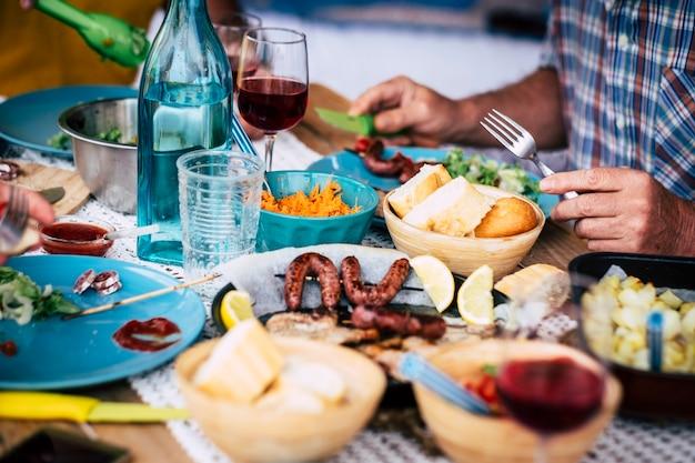 Großer tisch voller essen, brot, fleisch, gemüse... - einige leute sitzen neben dem tisch und essen und trinken wein und wasser - feiern - viel salat und alle arten von essen