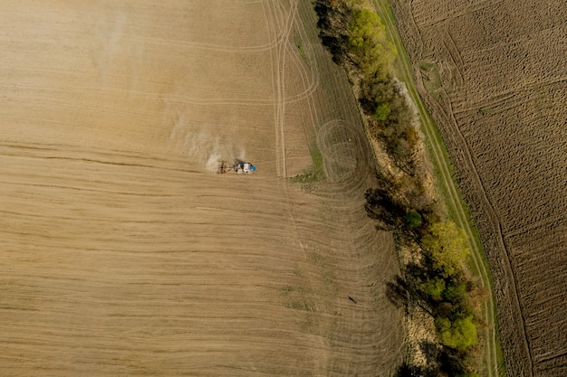 Großer traktor der luftaufnahme, der ein trockenes feld kultiviert. top-down-luftbildtraktor, der boden kultiviert und ein trockenes feld aussät.