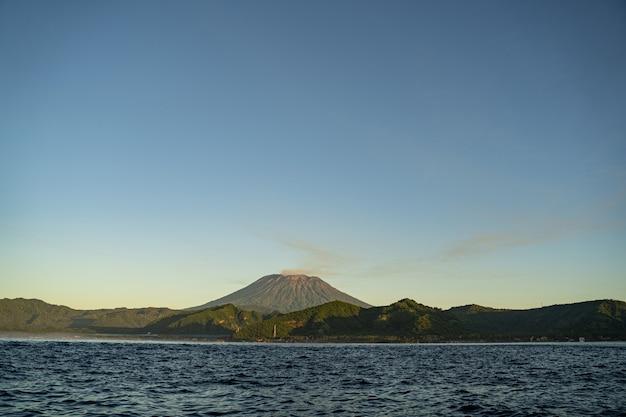 Großer vulkan zwischen grünen tropischen klippen