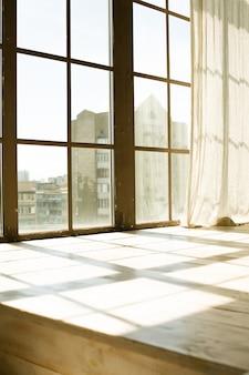Großes altes holzfenster mit transparentem vorhang im sonnenlicht