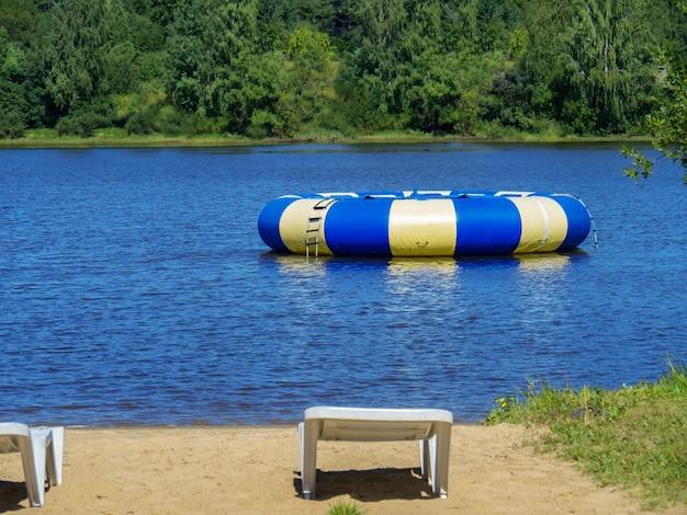 Großes aufblasbares rundes blaues trampolin an einem sonnigen tag im teich