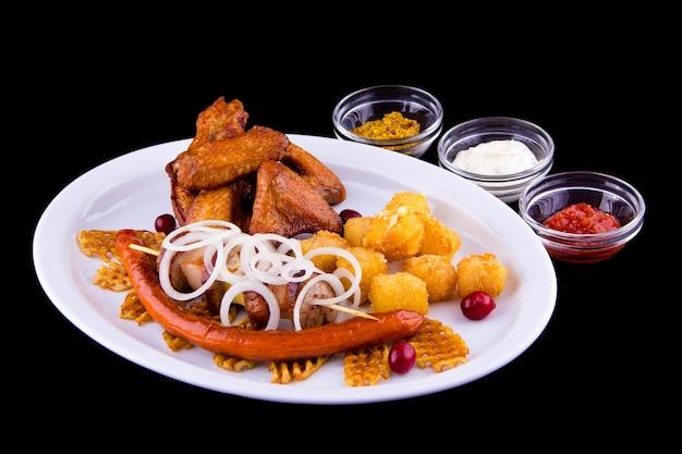 Großes bierset mit gebratenen snacks - hühnerflügel, schweinefleischspieß, hausgemachte würste, kartoffelchips, frittierter käse, zwiebeln, drei saucen: weiß, rot, senf.