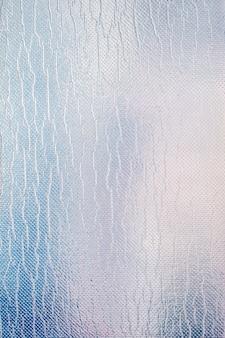 Großes blatt aus glänzender silber- oder zinnfolie. grauer glänzender hintergrund.