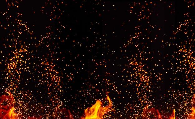 Großes brennendes lagerfeuer mit flammen und orangefarbenen funken, die in verschiedene richtungen fliegen