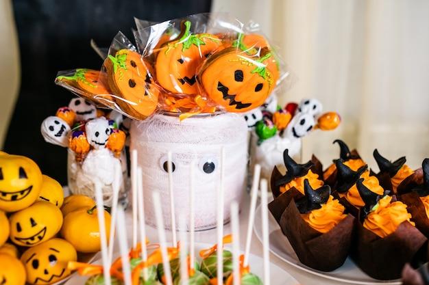 Großes dekoriertes glas mit kürbis-marshmallows auf dem schokoriegel zur feier von halloween.