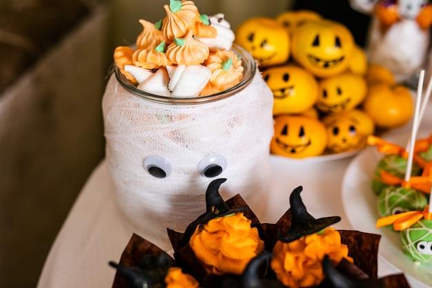 Großes dekoriertes glas mit kürbis-marshmallows auf dem schokoriegel zur feier von halloween