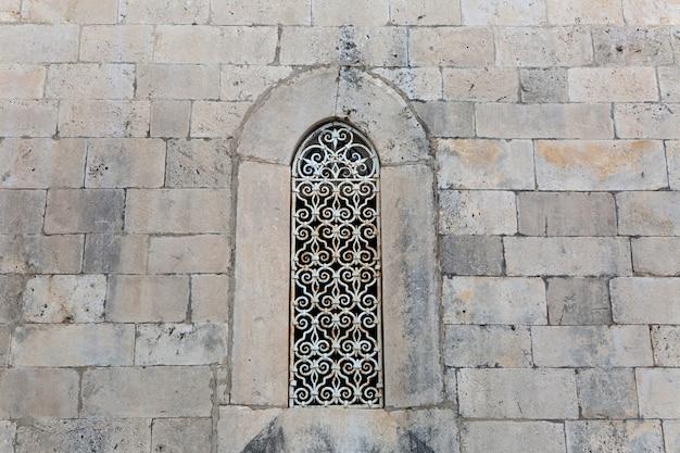 Großes fenster mit geschnitzten eisenstangen im alten backsteingebäude aus hellem stein