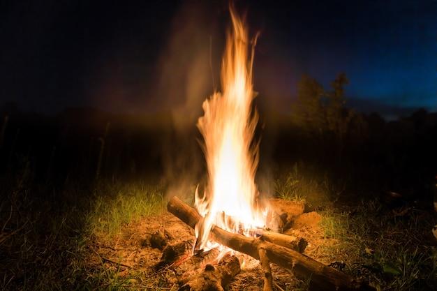 Großes feuer im orangefarbenen lagerfeuer bei sonnenuntergang mit blauem dunklem nachthimmel