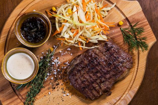 Großes fleischsteak mit gemüse, grün und soßen auf holztisch im luxusrestaurant