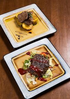 Großes fleischsteak mit gemüse und soßen in der quadratischen platte auf holztisch im luxus-restau