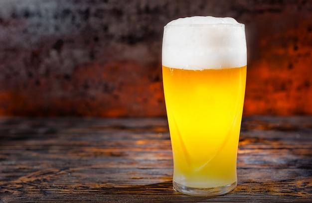Großes gefrorenes glas mit frisch gegossenem hellem, ungefiltertem bier und schaumstoffkopf auf dunklem holzschreibtisch. lebensmittel- und getränkekonzept