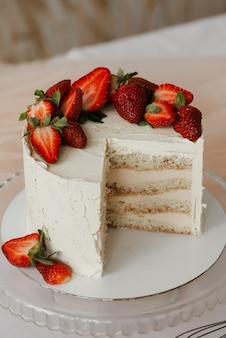 Großes geschnittenes stück weißer kuchen mit erdbeeren