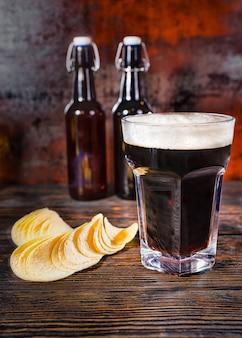 Großes glas frisch eingegossenes dunkles bier gegen zwei bierflaschen in der nähe von pommes auf dunklem holzschreibtisch. lebensmittel- und getränkekonzept