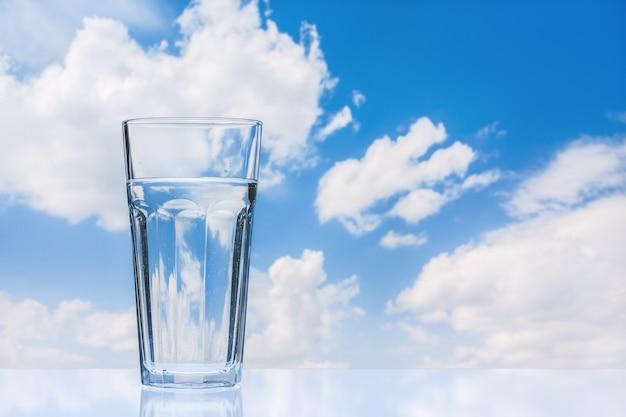 Großes glas frisches wasser gegen blauen himmel mit wolken. reflektierende oberfläche. speicherplatz kopieren.