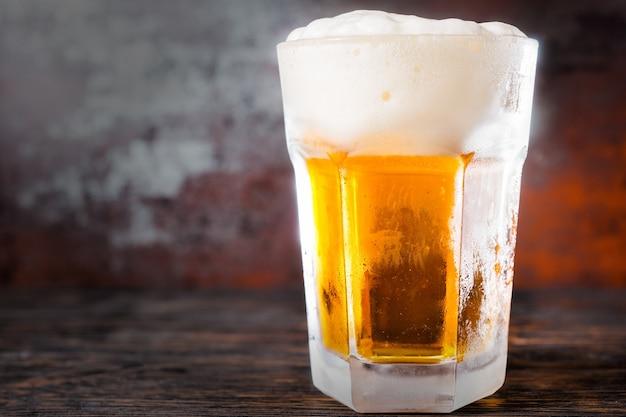 Großes glas mit einem hellen bier und einem großen schaumkopf auf einem alten dunklen schreibtisch. getränke- und getränkekonzept