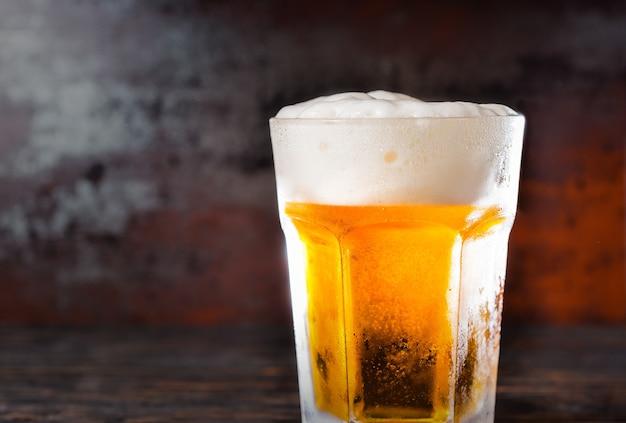 Großes glas mit einem hellen bier und einem schaumkopf auf einem alten dunklen schreibtisch. getränke- und getränkekonzept