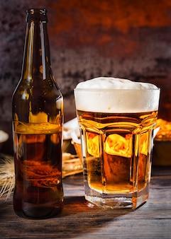 Großes glas mit frisch eingegossenem bier und schaumkopf in der nähe von flasche und tellern mit snacks auf dunklem holzschreibtisch. lebensmittel- und getränkekonzept