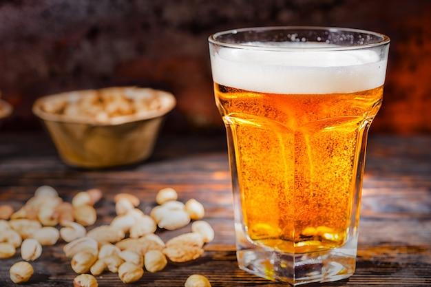 Großes glas mit frisch eingegossenem hellem bier in der nähe von tellern mit snacks und verstreuten nüssen auf einem dunklen holzschreibtisch. lebensmittel- und getränkekonzept