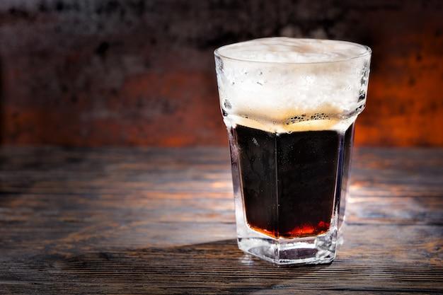Großes glas mit frisch gegossenem dunklem bier und schaumkopf auf holzschreibtisch. lebensmittel- und getränkekonzept