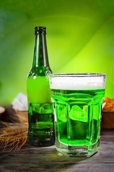 Großes glas mit frisch gegossenem grünem bier und schaumkopf in der nähe von flasche und tellern mit snacks auf dunklem holzschreibtisch. lebensmittel- und getränkekonzept