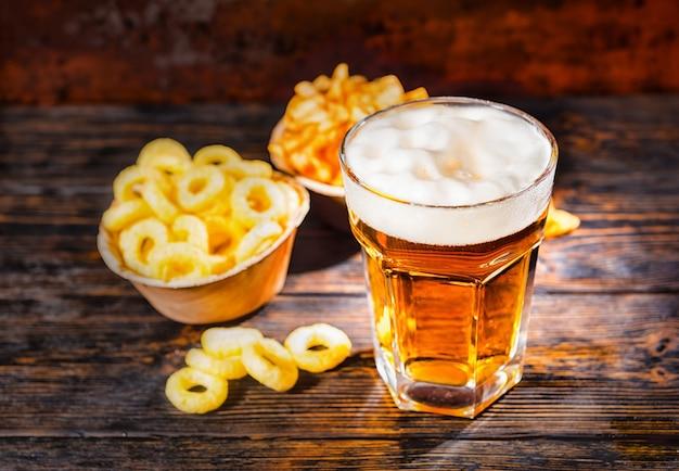 Großes glas mit frisch gegossenem hellem bier in der nähe von tellern mit snack und pommes auf dunklem holzschreibtisch. lebensmittel- und getränkekonzept