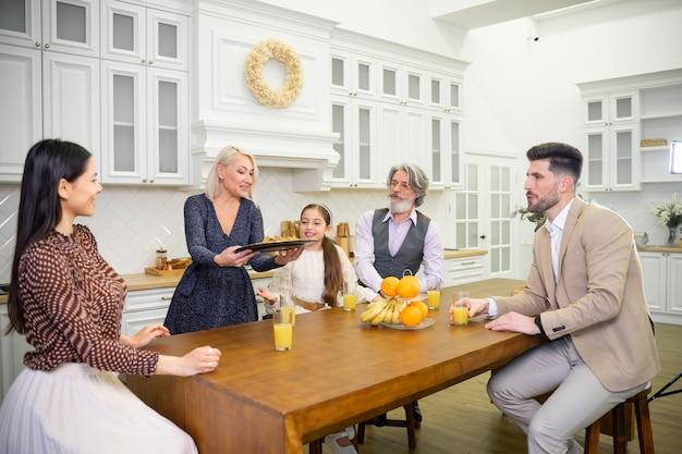Großes glückliches familientreffen zur geburtstagsfeier am küchentisch