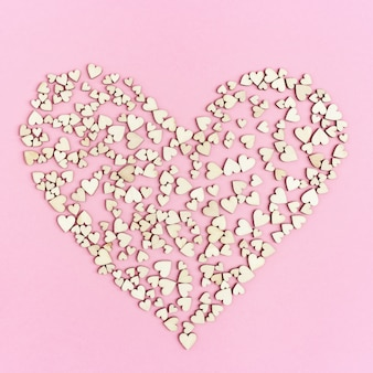 Großes herz besteht aus vielen kleinen herzen auf rosa. konzept der liebe und romantischen beziehung.