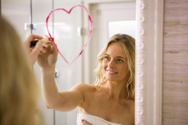 Großes herz der schönen blondine zeichnung auf spiegel im badezimmer zu hause