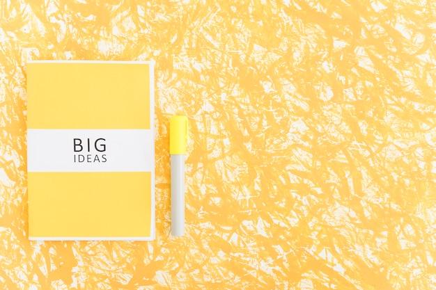 Großes ideentagebuch und -markierung auf strukturiertem gelbem hintergrund