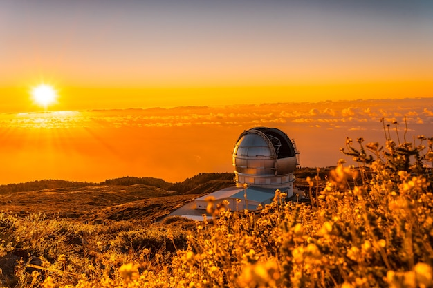 Großes kanarisches teleskop namens grantecan optico del roque de los muchachos in der caldera de taburiente in einem wunderschönen orangefarbenen sonnenuntergang, la palma, kanarische inseln. spanien