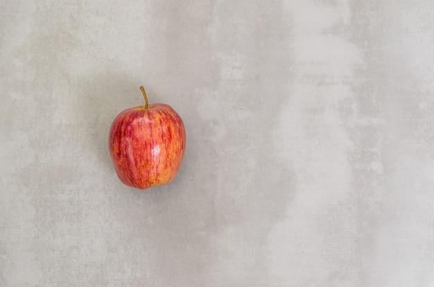 Großes konzept der gesunden ernährung, apfel im grauen hintergrund. mit kopierplatz.