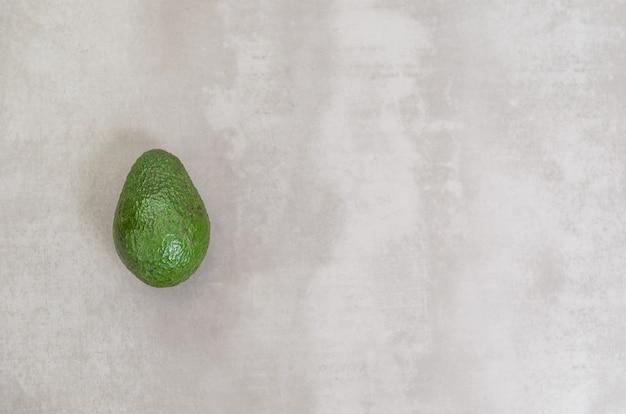 Großes konzept der gesunden ernährung, avocado im grauen hintergrund. mit kopierplatz.
