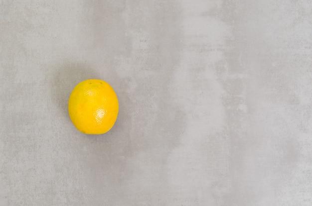 Großes konzept der gesunden ernährung, orange im grauen hintergrund. mit kopierplatz.
