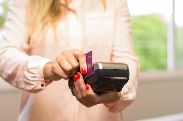 Großes konzept der zahlung mit kreditkarte, junge kaukasische frau, die zahlung mit kreditkarte auf maschine macht.