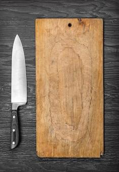 Großes küchenmesser, das auf einem alten schneidebrett liegt