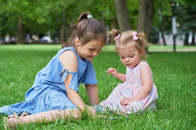 Großes mädchen und ein kleines mädchen sitzen auf dem grünen gras und schauen auf das telefon