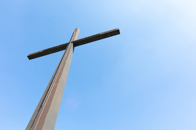 Großes metallkreuz und klarer himmel - das konzept der religion