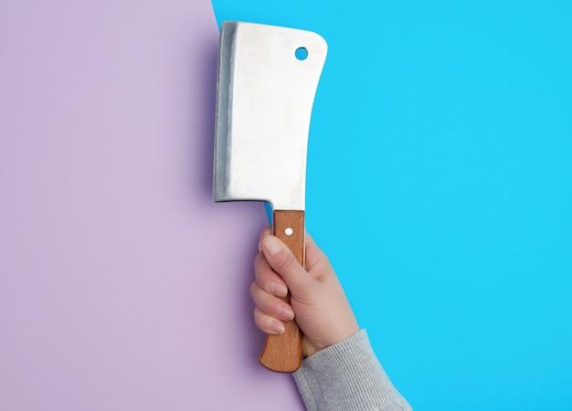 Großes metallmesser zum schneiden von fleisch in der hand