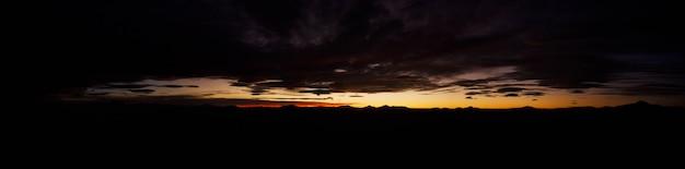 Großes natürliches panorama der salzwiesen salar de uyuni in bolivien bei sonnenuntergang. erstaunliche farbenfrohe aussicht auf die untergehende sonne am späten abend bei gutem wetter. konzept der reise. copyright-bereich für die website