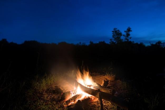Großes orangefarbenes feuer im lagerfeuer bei sonnenuntergang mit blauem dunklem nachthimmel