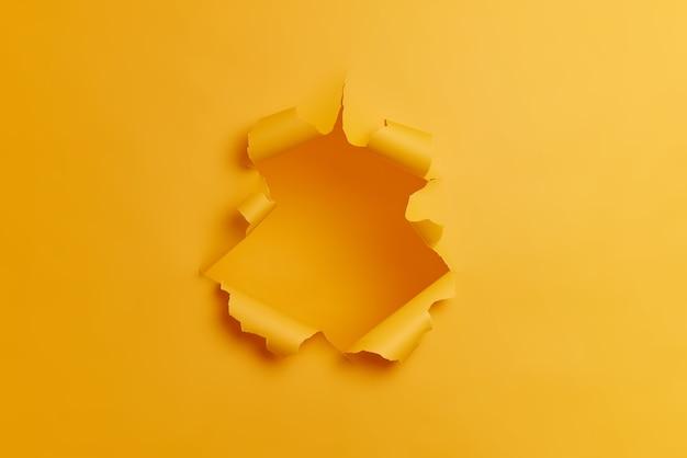 Großes papierloch in der mitte des gelben hintergrunds. zerrissene zerrissene studiowand. durchbruchkonzept. keine leute im schuss.