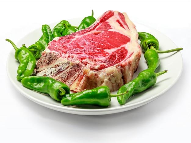 Großes rohes kotelett der kuh mit grünen paprikas auf platte und weiß