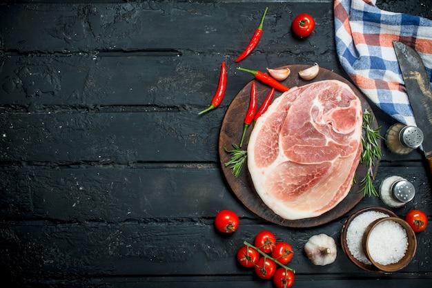 Großes rohes schweinesteak mit gewürzen und gemüse auf einem schwarzen rustikalen tisch.