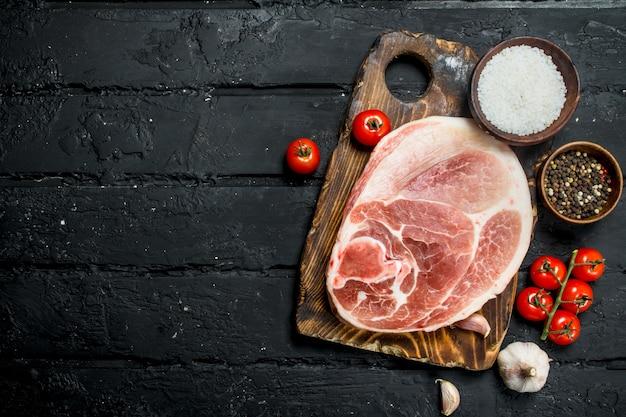 Großes rohes schweinesteak mit tomaten und gewürzen. auf einem schwarzen rustikalen.