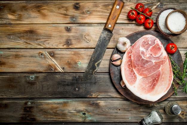 Großes rohes stück schweinefleisch mit gewürzen und kräutern. auf einem hölzernen hintergrund.