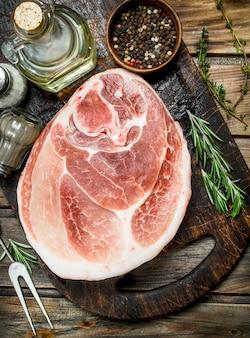 Großes rohes stück schweinefleisch mit gewürzen und kräutern. auf einem holz.