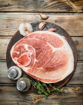 Großes rohes stück schweinefleisch mit gewürzen und kräutern. auf einer holzoberfläche.