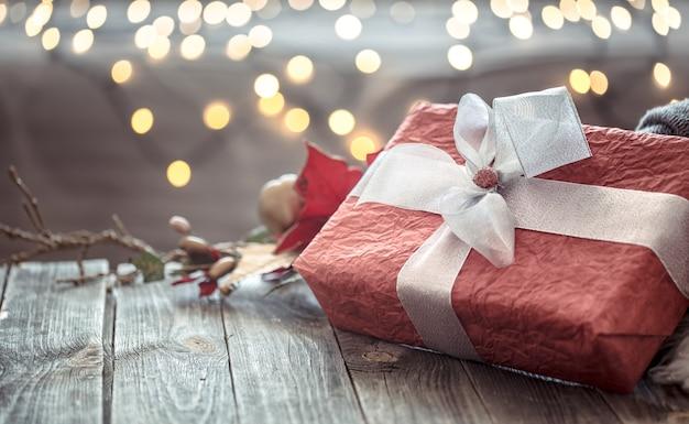 Großes rotes geschenk über weihnachtslichtern bokeh im haus auf holztisch mit pullover auf hintergrund und dekorationen. winterstimmung, weihnachtsdekoration, magische weihnachten.