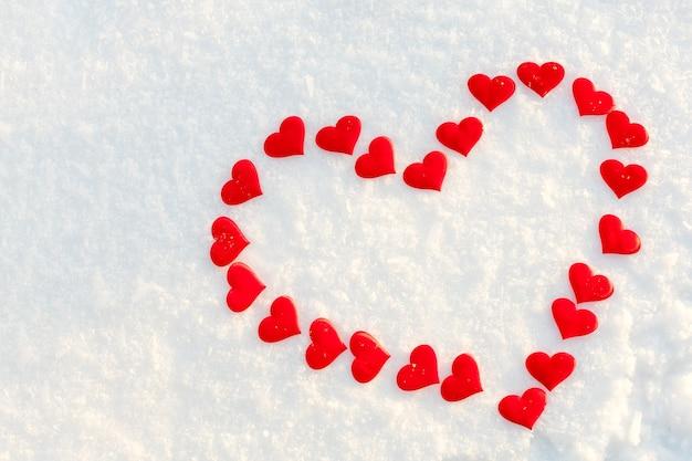 Großes rotes herz auf weißem sauberem schnee im sonnigen wintertag.